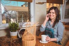 Yang kobiety napoju ładna herbata podczas gdy opowiadający telefon Zdjęcia Stock