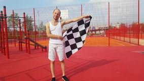 Yang man with finish flag. Yang man with finish checkered flag outdoors stock video footage