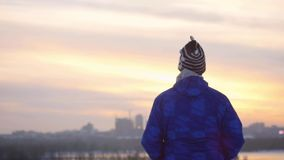 Yang man standing outdoor and looking on sunset in the urban city on reflected in river background in slowmotion. 1920x1080. hd stock video