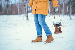 Yang woman holding retro camera. Outdoor in winter day royalty free stock photo