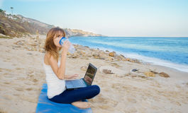 Yang woman with laptop by the ocean Stock Photo