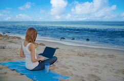 Yang woman with laptop by the ocean Stock Photos
