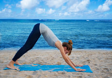 Yang woman practicing yoga by the ocean. Young pretty woman practicing yoga on the beach by the ocean Stock Photography