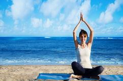 Yang woman practicing yoga by the ocean. Young pretty woman practicing yoga on the beach by the ocean Stock Photos