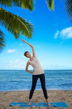 Yang woman practicing yoga by the ocean. Young pretty woman practicing yoga on the beach by the ocean Stock Images