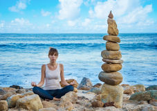 Yang woman practicing yoga by the ocean Royalty Free Stock Photography