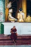 Yangon, το Μιανμάρ - 19 Φεβρουαρίου 2014: Ο μοναχός διαβάζει μπροστά από το te στοκ φωτογραφίες