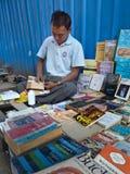 YANGON, BURMA - DECEMBER 23, 2013 - View of Sidewalk Bookseller. View of a sidewalk bookseller repairing a book at his table in Yangon, Myanmar where he sells Stock Photography