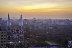 Yangon dawn. Wide view of sprawling Asian city with church in foreground under orange sky at sunrise stock photos