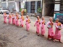 YANGON, MYANMAR - APRIL 17, 2013: De boeddhistische nonnen lopen bij t royalty-vrije stock afbeeldingen