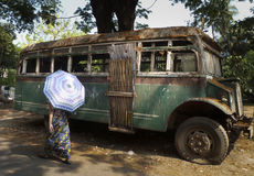 Yangon, Myanmar - April 18, 2014 - Unidentified woman with umbre. An unidentified woman with an umbrella walks past a broken down vintage green bus on a Yangon Royalty Free Stock Images