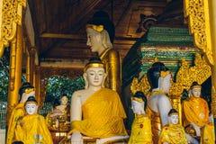 Yangon, Myanmar - 19 de fevereiro de 2014: Feche acima do statu dourado de buddha Imagens de Stock