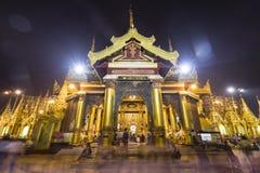 YANGON, MYANMAR, December 25, 2017: Side temple with Buddhists beside Shwedagon Pagoda. YANGON, MYANMAR, December 25, 2017: Side temple with Buddhists beside the Stock Photos