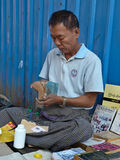 YANGON, MYANMAR - DECEMBER 23, 2013: Street bookseller repairs a. A street bookseller in Yangon, Myanmar (Burma) repairs a paperback while minding his display Stock Images