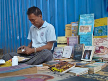 YANGON, MYANMAR - DECEMBER 23, 2013: A street bookseller sits am. Medium close up of a street bookseller in Yangon, Myanmar (Burma) repairs a paperback while Stock Photos