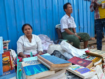 YANGON, MYANMAR - DECEMBER 23, 2013: Street booksellers are seen. A female and male street bookseller seen sitting behind a table of used and second hand novels Royalty Free Stock Images