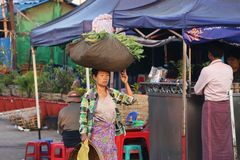 Myanmese woman with thanakha Myanmar powder on her face put big fabric pack of vegetable on her head to bring to sell at the. Yangon, Myanmar, Feb 24, 2019 stock photos