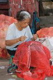 Old lady in Myanmar sitting and sewing the red sack stock photos