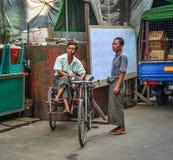 Pedicab driver on street stock image
