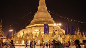 Time lapse night shot of people walking at The Shwedagon Pagoda, also known as the Golden Pagoda. stock video