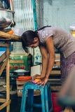 Yangon Myanmar - FEBRUARI 19th 2014: Burmese kvinnlig gatamat försäljer Arkivfoto