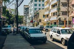 Yangon Myanmar - FEBRUARI 19th 2014: Gatasikt av taxien och bilar på Arkivfoton