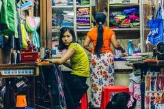 Yangon Myanmar - FEBRUARI 19th 2014: Kvinnor i en torkduk shoppar stallen av Royaltyfri Bild