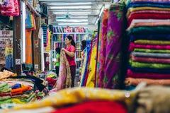Yangon Myanmar - FEBRUARI 19th 2014: Kvinnor i en torkduk shoppar stallen av Arkivbild