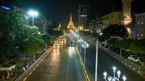 Evening Sule road in Yangon, Myanmar. YANGON, MYANMAR - FEBRUARY 14, 2018: Evening traffic along Sule road, located in Downtown, the giant golden Sule Pagoda is stock footage