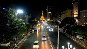 Night in Yangon Downtown, Myanmar. YANGON, MYANMAR - FEBRUARY 15, 2018: The evening view of Sule road with numerous public buses and the huge golden brightly stock footage