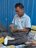 YANGON MYANMAR, GRUDZIEŃ, - 23, 2013: Uliczny księgarz naprawia a obrazy stock