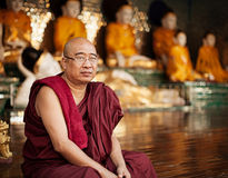 YANGON, MYANMAR - 03 JAN 2014: monk sits near a Buddhist c Royalty Free Stock Images