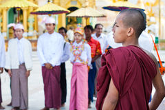 YANGON MYANMAR - JANUARI 29: Den unga buddistiska munken observerar novicationceremonin på den Shwedagon templet Januari 29, 2010 Arkivfoton