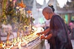 YANGON, MYANMAR - JANUARI 29: Een boeddhistische monnik steekt joss stickat de tempel 29 Januari, 2010, Myanmar van Shwedagon aan Stock Foto's