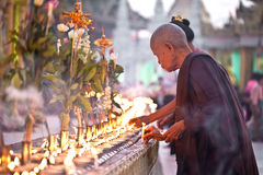 YANGON MYANMAR - JANUARI 29: En buddistisk munk tänder den jossstickatShwedagon templet Januari 29, 2010, Myanmar Arkivfoton