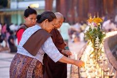 YANGON MYANMAR - JANUARI 29: En kvinnabuddist tänder en olje- lampa på den Shwedagon templet Januari 29, 2010, Myanmar Royaltyfria Bilder