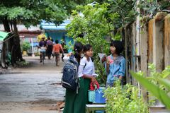Three girl students in Myanmarese uniform of school white shirt and green Long Yi Discuss the subject of homework. stock images