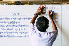 Yangon, Myanmar - March 2019: Burmese man writing temple ceremony schedule on the white board royalty free stock image