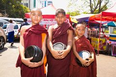 Three unidentified young novice monks walking morning alms in Ya. YANGON, MYANMAR-MARCH 3, 2017: Three unidentified young novice monks walking morning alms in royalty free stock image