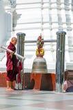 YANGON, MYANMAR - NOVEMBER 25, 2015 - Buddhist monk ringing the Stock Images