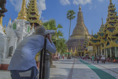 Yangon, Myanmar on November 07, 2014 - Shwedagon pagoda. The guy looks at the restoration of the Shwedagon pagoda Stock Images