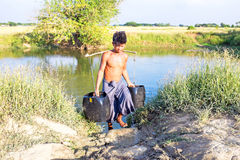 Yangon, Myanmar - November 18, 2015: Water carrier with two buckets getting water in the countryside Stock Photography
