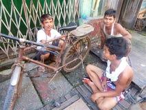 YANGON, MYANMAR - OCTOBER 1, 2013 - A bicycle repairman and his Stock Images