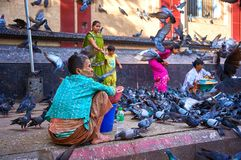 Indian family surrounded with pigeons. Two nearby vendors are ready to sell them pigeon food. Yangon, Myanmar - 21 October, 2017: Indian passerby family Royalty Free Stock Photo
