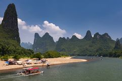 Boats and rafts with tourists cruising in the Li River with the tall limestone peaks in the background near Yangshuo in China Stock Photos