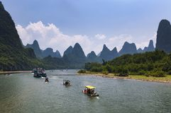 Boats with tourists cruising in the Li River with the tall limestone peaks in the background near Yangshuo in China Royalty Free Stock Photo