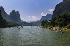 Boats with tourists cruising in the Li River with the tall limestone peaks in the background near Yangshuo in China Royalty Free Stock Images
