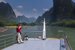 Chinese man in a boat cruising in the Li River and photographing the the tall limestone mountains near Yangshuo in China. Yangshuo, China - August 1, 2010 Royalty Free Stock Photo