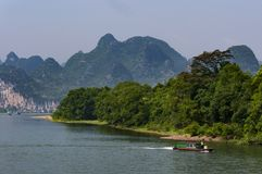 Small boat in the Li River with the tall limestone peaks in the background near Yangshuo in China Stock Photography