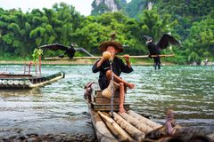 Yangshuo, China - July 27, 2018: Cormorant Fisherman On A Bamboo Rafts On Li River In Yangshuo Near Guilin In China Stock Image
